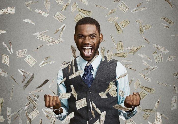Ein Mann im Anzug steht in einem Regen aus Dollarscheinen und freut sich enthusiastisch.